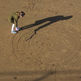 Drawing with a stick and with her shadow!